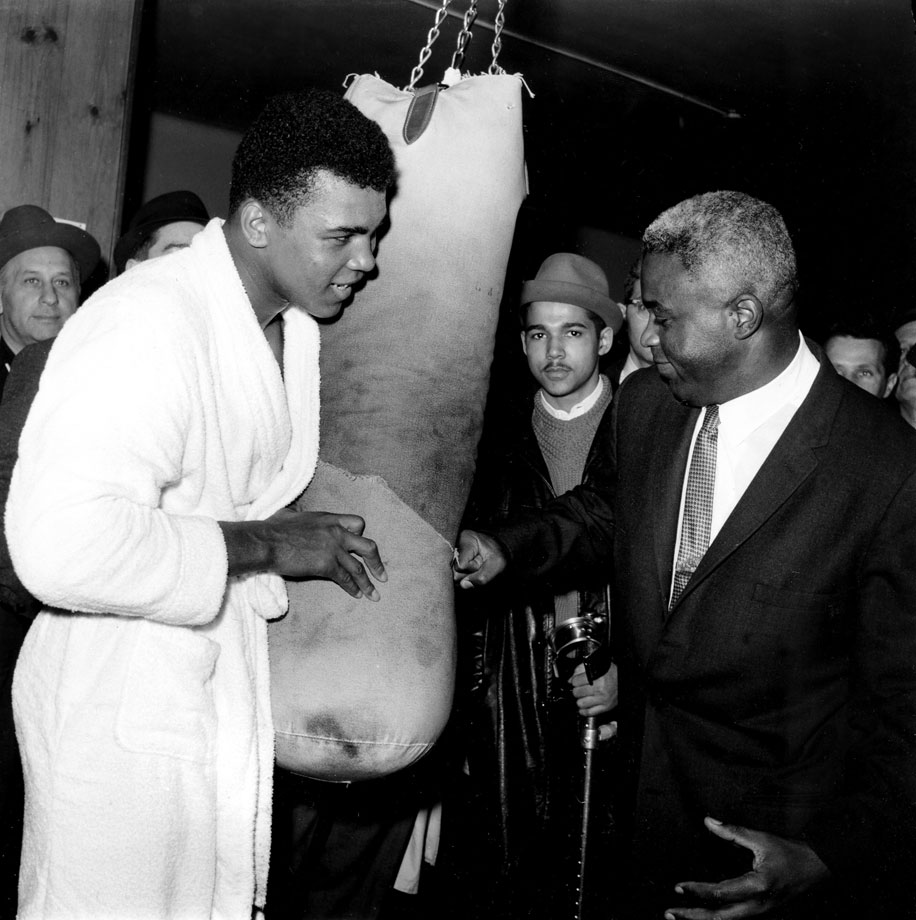Jackie Robinson hits a punching bag held by Muhammad Ali, then Cassius Clay, in a New York gym in March 1963. Less than a year later, Clay would win the world heavyweight title with a victory over Sonny Liston.