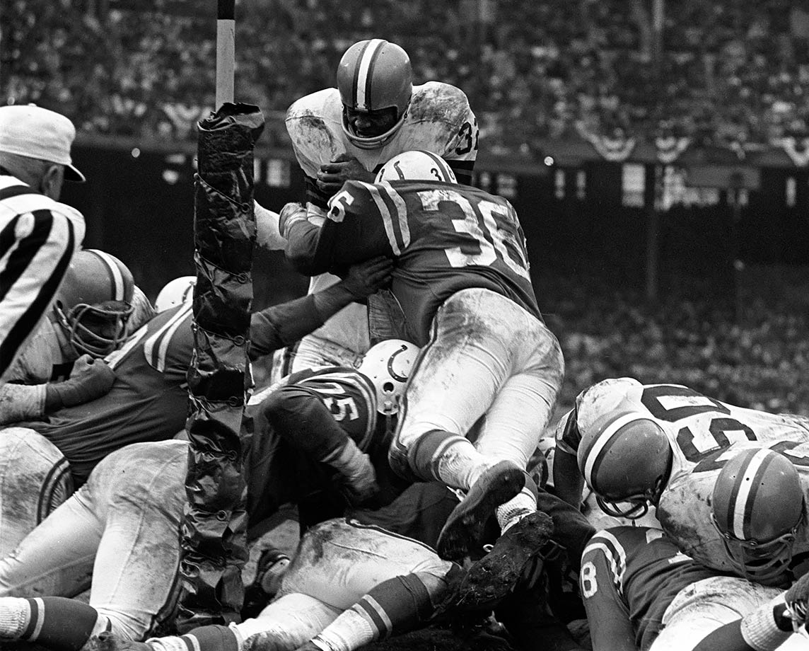 Jim Brown attempts to leap over the pile against the Baltimore Colts in the 1964 NFL Championship Game. He gained 114 yards on 27 carries as the Cleveland Browns routed the Colts 27-0. It was the only championship of Brown's career.