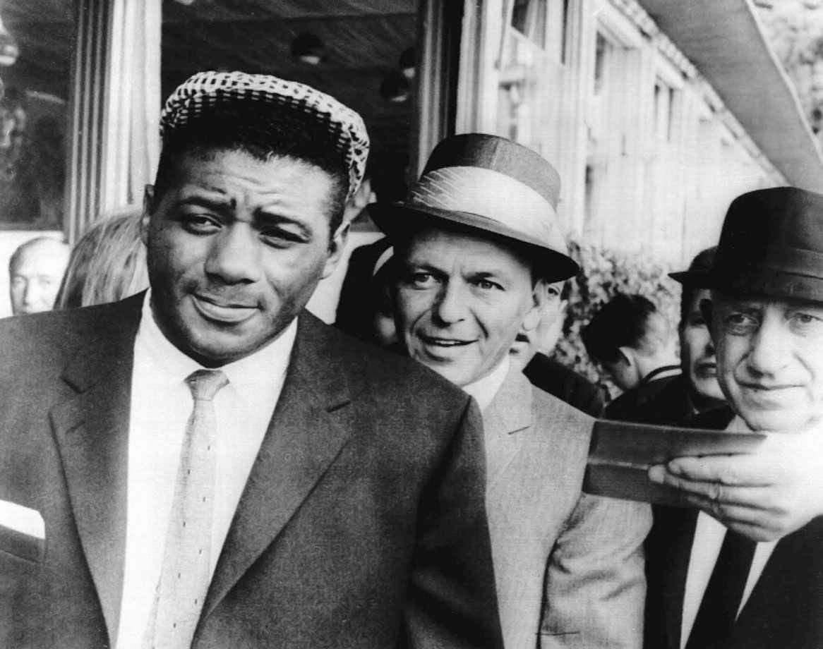 Frank Sinatra stands with former world heavyweight champion Floyd Patterson the day after Patterson's non-title bout victory over Eddie Machem in Stockholm, Sweden, on July 6, 1964.
