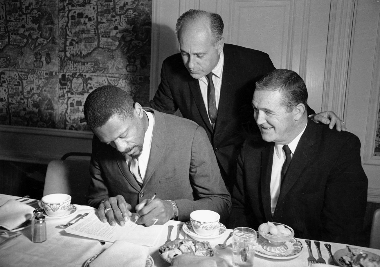 As team president Jack Waldron and coach/general manager Red Auerbach look on, Bill Russell signs a three-year contract with the Celtics. He was coming off a season in which he had won his fifth MVP award and led the Celtics to their seventh straight championship.