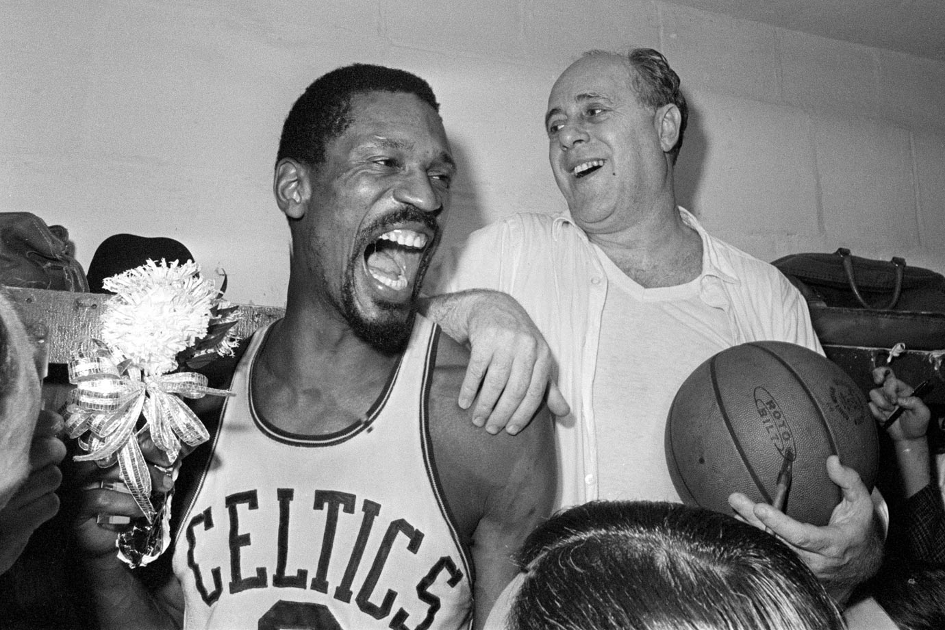 Bill Russell holds a corsage as he and coach Red Auerbach celebrate the Celtics eighth straight title. The team defeated the Lakers 95-93 to win the crown.