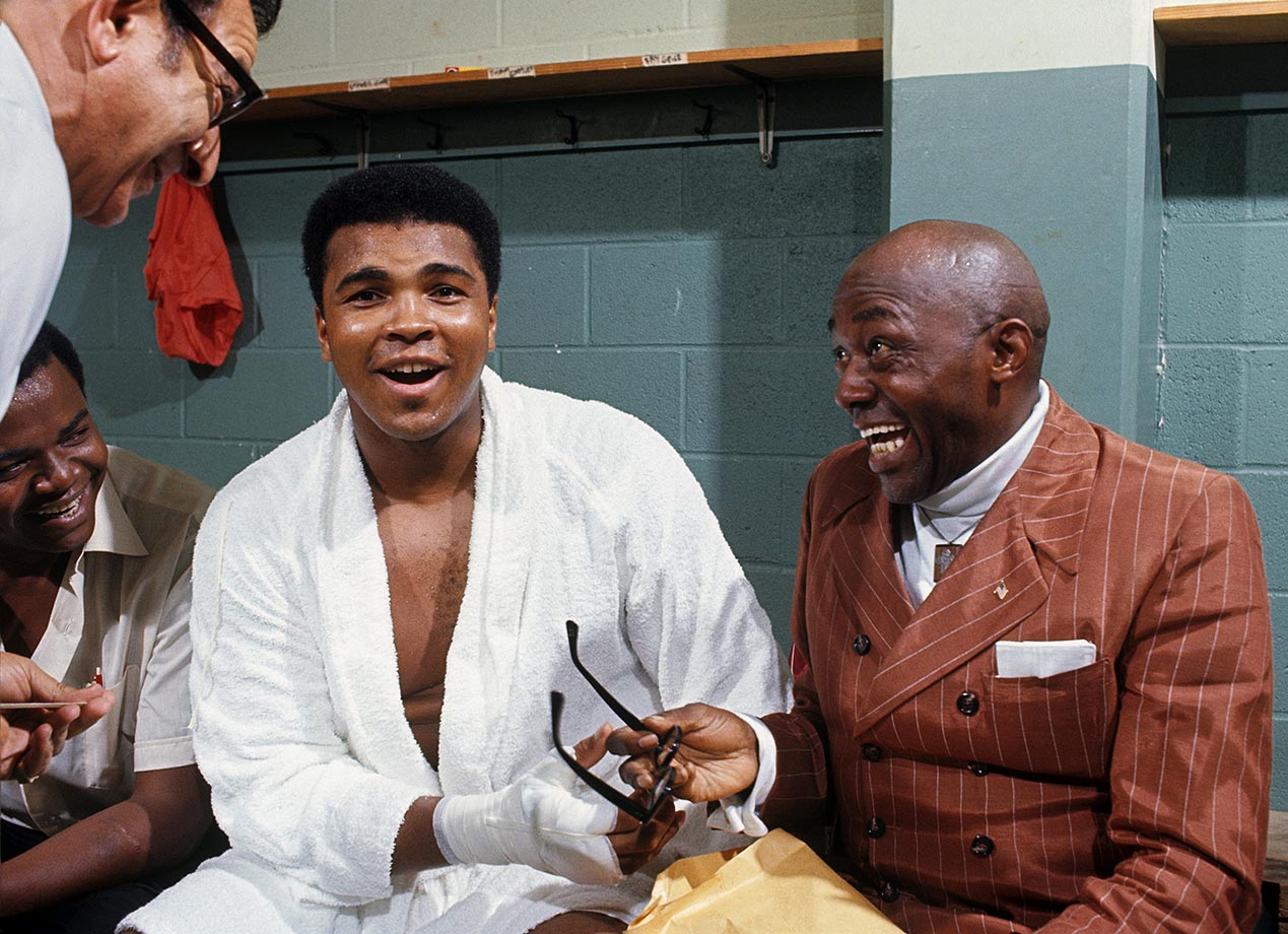 In professional exile for three and a half years because of his draft case, Ali sought to return to boxing in 1970. He began with a night of exhibition bouts at Morehouse College in Atlanta, where before going into the ring, he shared a locker room laugh with actor and comedian Lincoln Perry (right), better known by his stage name of Stepin Fetchit. The friendship between the two black icons would later be examined in an acclaimed play by Will Power, Fetch Clay, Make Man.