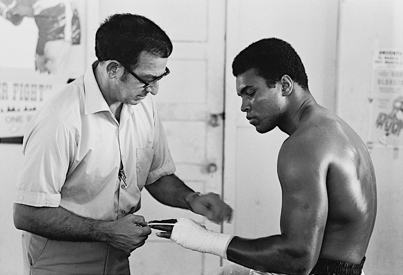 After the Atlanta Athletic Commission at last granted Ali a license, the deposed champion went back into serious training. He was, as ever, in the capable hands of trainer Angelo Dundee, here wrapping boxing's most famous fists at the 5th Street Gym in Miami in October 1970.