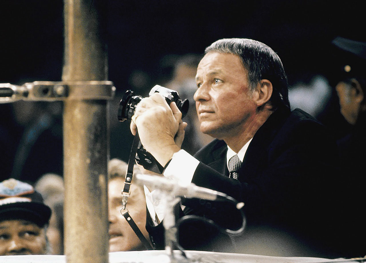 "Frank Sinatra photographs Joe Frazier and Muhammad Ali's first bout, ""The Fight of the Century,"" from ringside at Madison Square Garden in New York City on March 8, 1971."