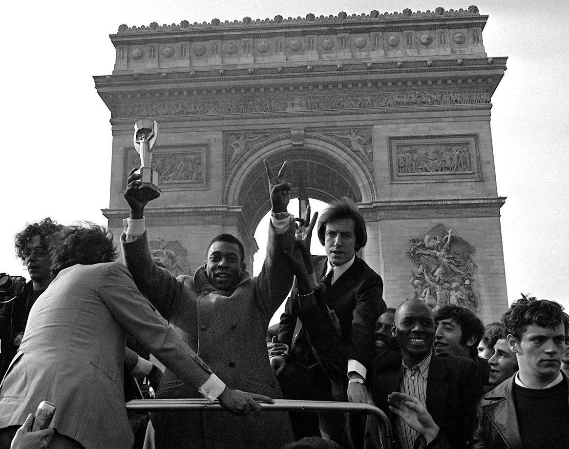 Pelé is paraded down the Champs Elysees boasting the Jules Rimet World Cup Trophy, which Brazil was awarded for their dominance in the 1970 tournament. He was in Paris with his Santos team for a 1971 charity match.