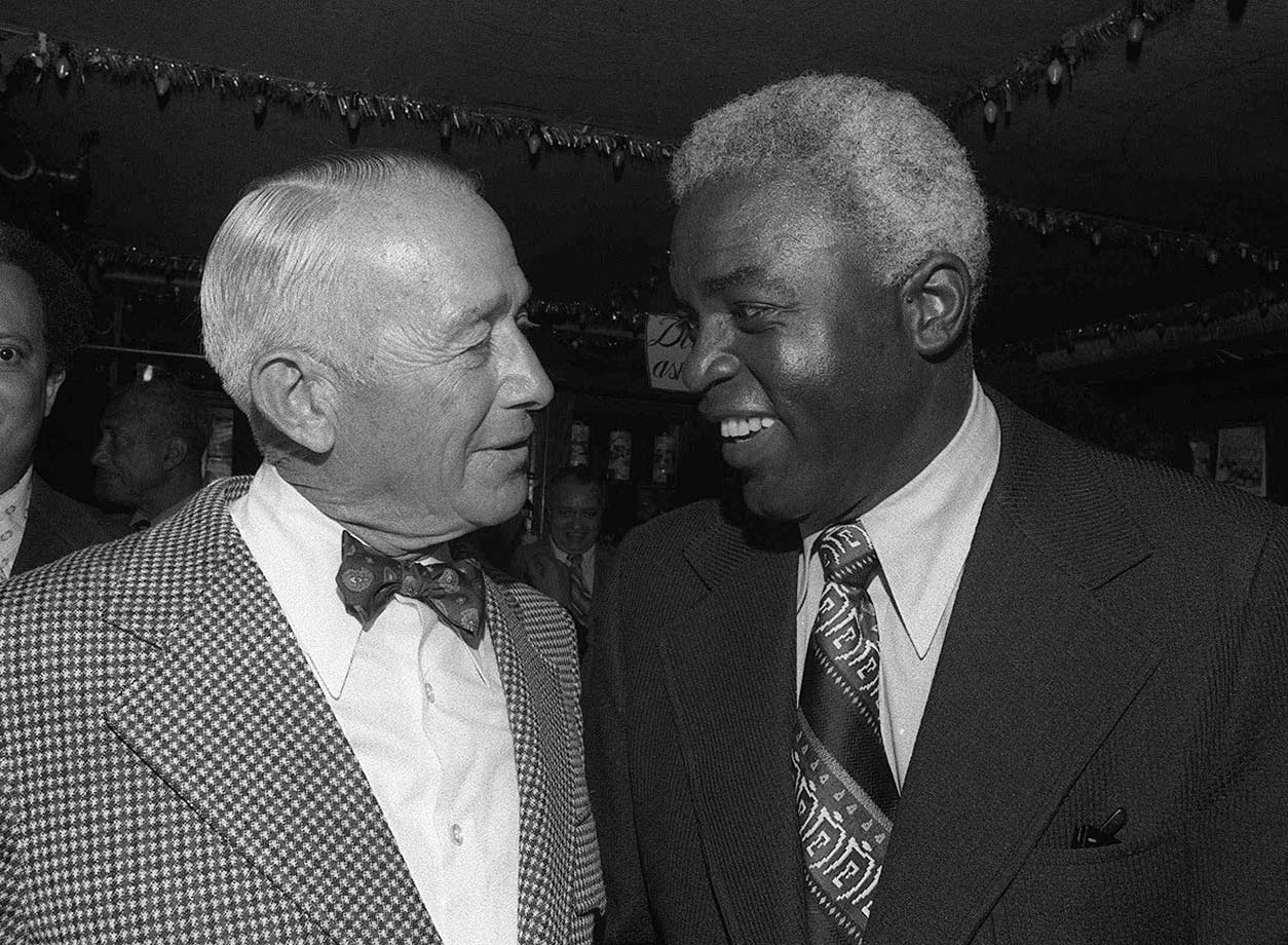 Clude Sukeforth, the scout who played a major role in bringing Jackie Robinson to the major leagues, speaks with Robinson during a luncheon honoring Robinson in New York on July 19, 1972.