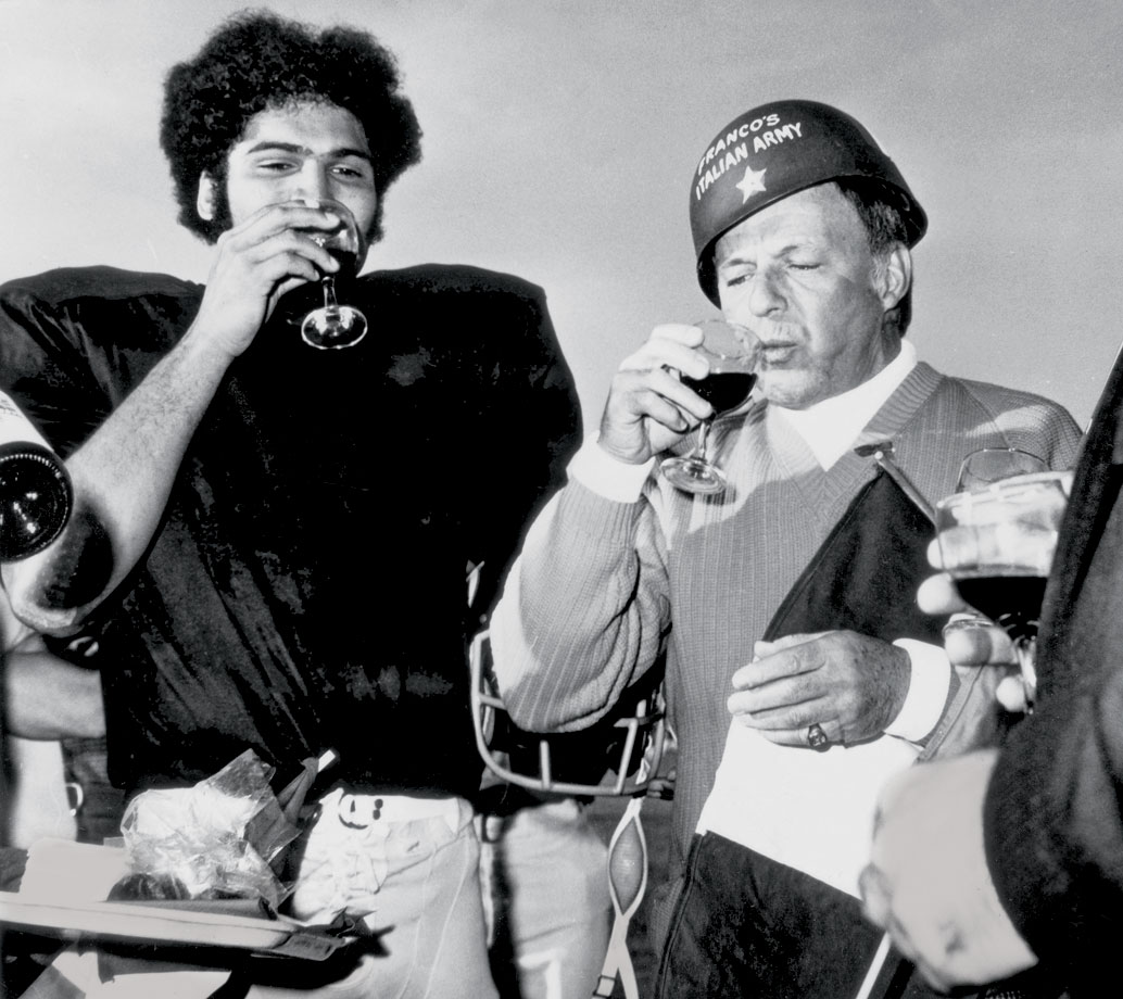 Franco Harris and Frank Sinatra have wine and cheese at a Pittsburgh Steelers practice after Sinatra was made a one-star general in Franco's Italian Army in Palm Springs, Calif., on Dec. 14, 1972.
