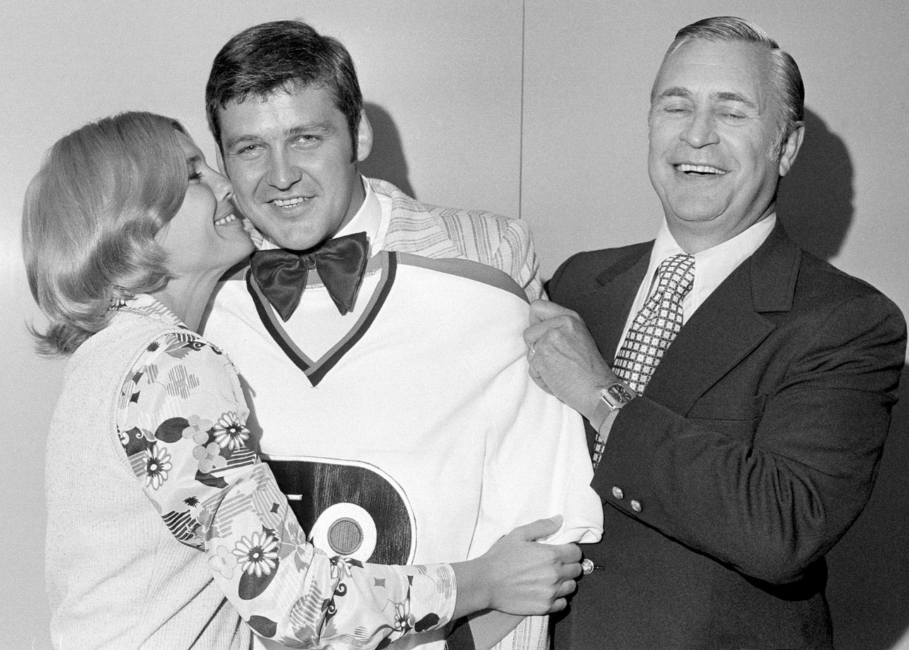 Seeking a return to the NHL, but not back in Toronto, the Maple Leafs traded Bernie Parent's NHL rights back to the Flyers for Doug Favell and a first round pick in the 1973 amateur draft. Here, Parent gets a congratulatory kiss from his wife, Carol, as Philadelhia GM Keith Allen grins while holding up a Flyers jersey.