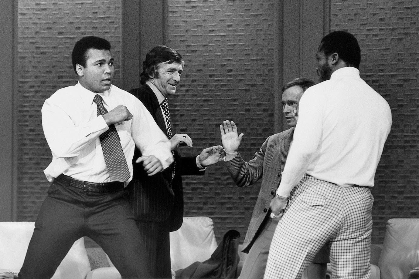 Ali and Joe Frazier fight on the set of The Dick Cavett Show while reviewing their 1971 bout in advance of their 1974 rematch. Ali called Frazier ignorant, to which Frazier took exception. As the studio crew tried to calm Frazier down, Ali held Frazier by the neck, forcing him to sit down and sparking a fight. The television set fight amped up anticipation of their January 1974 bout.
