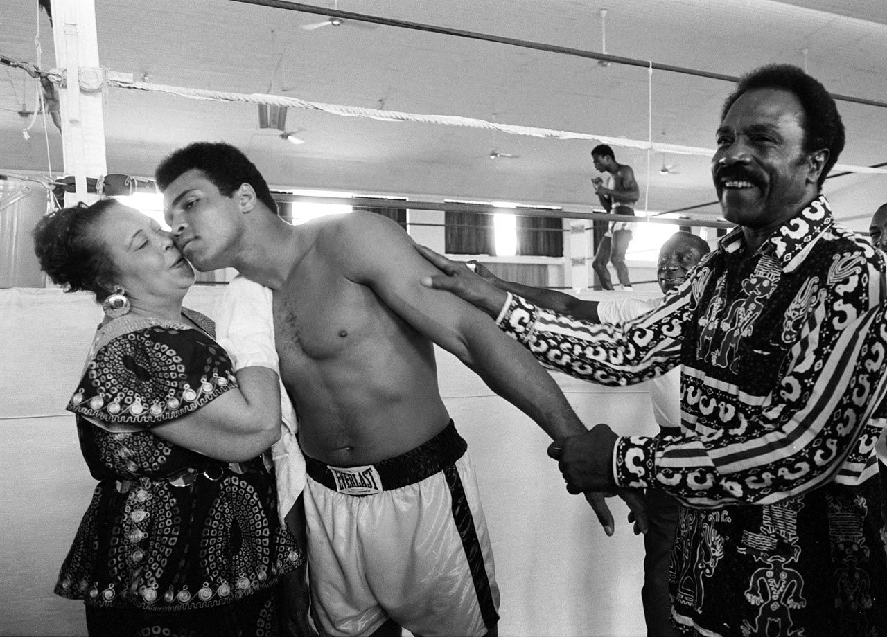 While training before his fight with George Foreman, Ali kisses his mother, Odessa Clay, while his father, Cassius Clay Sr., looks on. Ali's superior strategy and ability to take a punch led him to his upset victory as he absorbed body blows from Foreman before he responded with powerful combinations to Foreman's head.