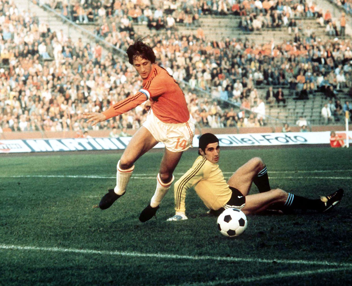"Dutch star Johan Cruyff fakes out a goalkeeper and scores in the 1974 World Cup.  Cruyff invented ""the Cruyff turn,"" one of soccer's coolest and most devastating tricks, cementing his place in soccer history."
