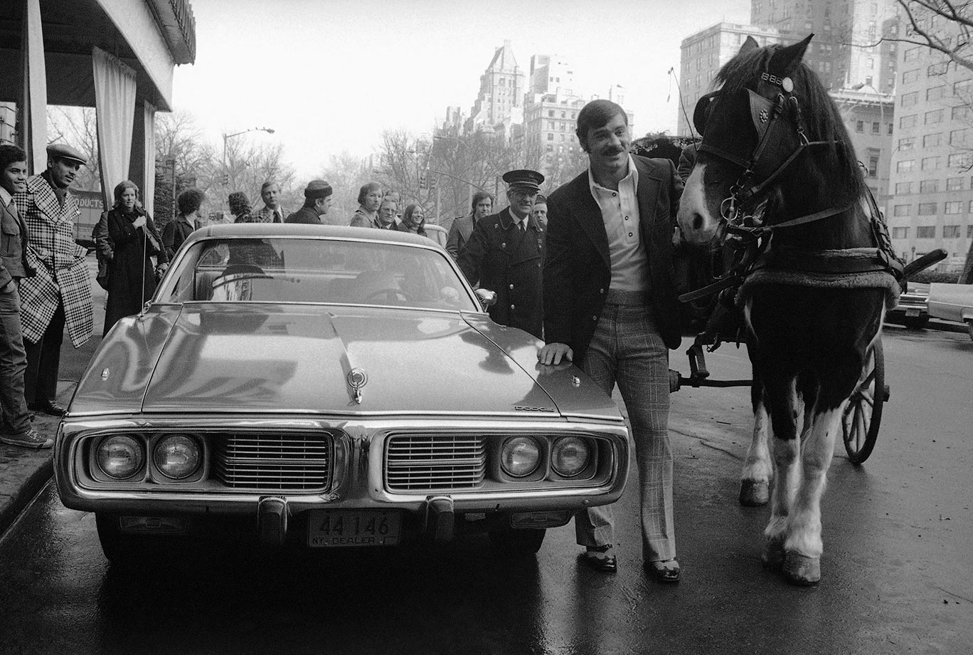 Larry Csonka, Miami Dolphins runner and Super Bowl hero, stands in a New York City street next to the car he received.
