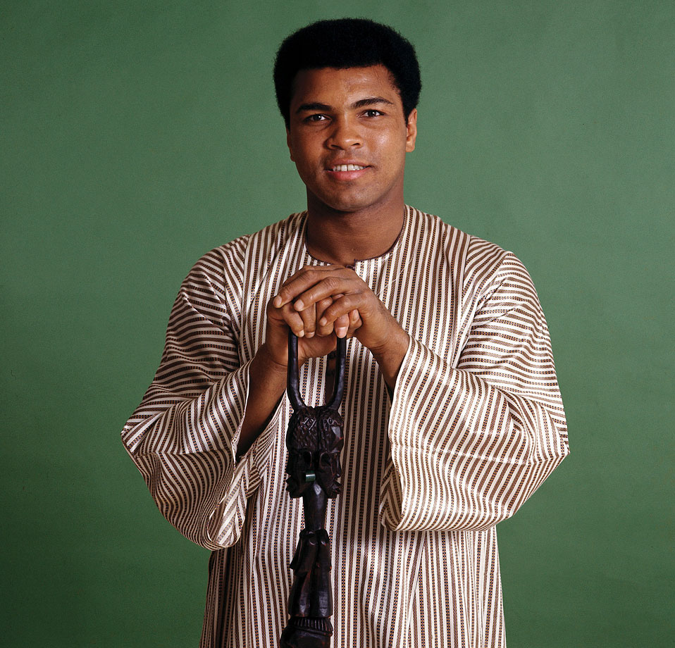 Muhammad Ali poses for a portrait after being selected as the Sports Illustrated Sportsman of the Year in 1974. Ali wore a dashiki, a men's garment widely worn in West Africa. He also brought the walking stick given to him by Zaire's president.