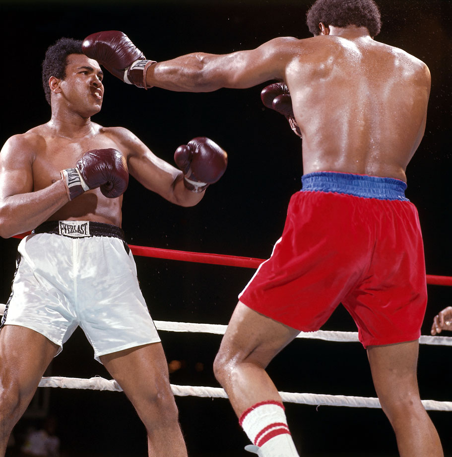 Muhammad Ali looks for his window as George Foreman tries to fend him off.
