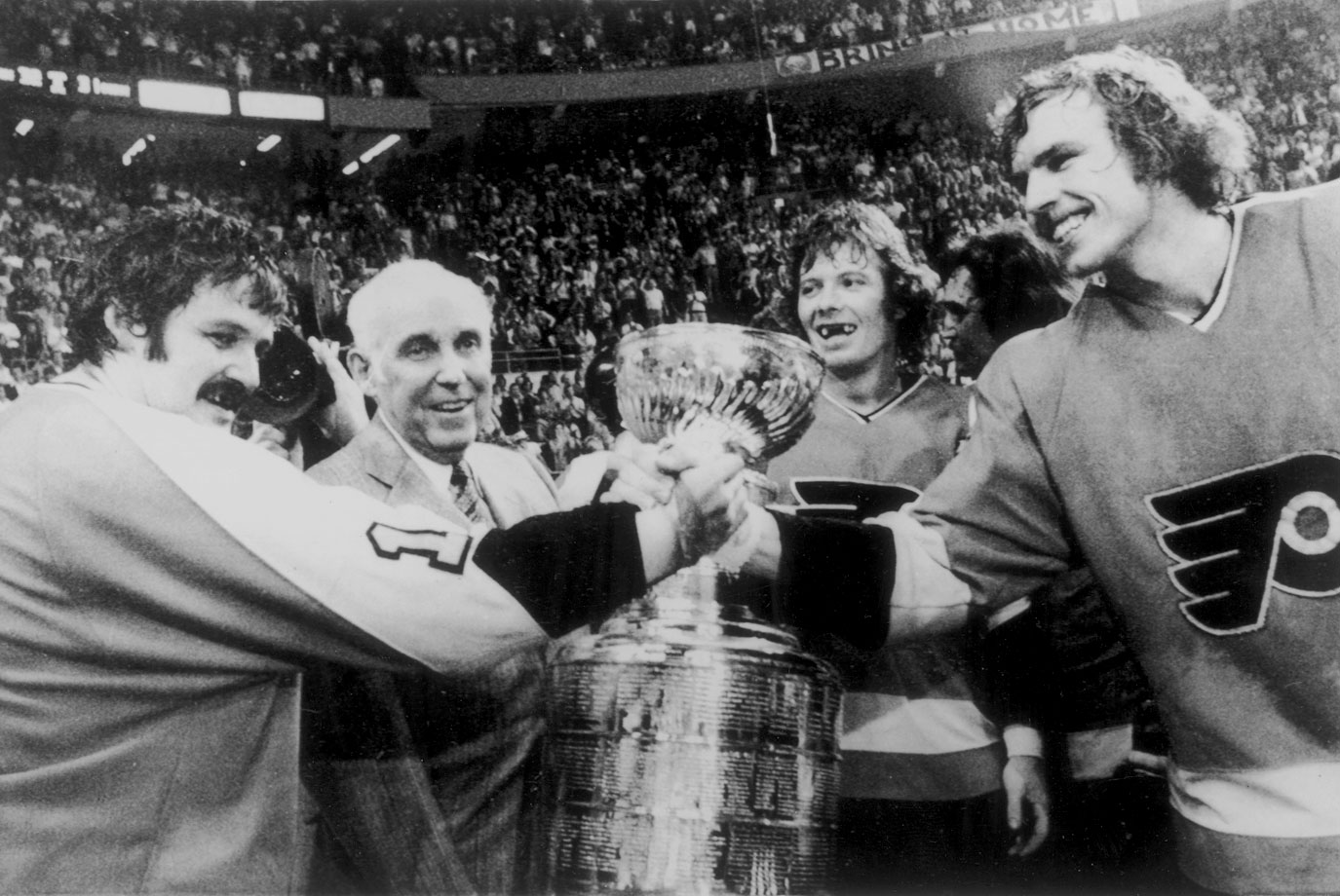 NHL President Clarence Campbell presents Bernie Parent, Bobby Clarke and Bill Clement with the Stanley Cup after their victory over the Sabres in Game 6 on May 27, 1975 in Buffalo, N.Y.