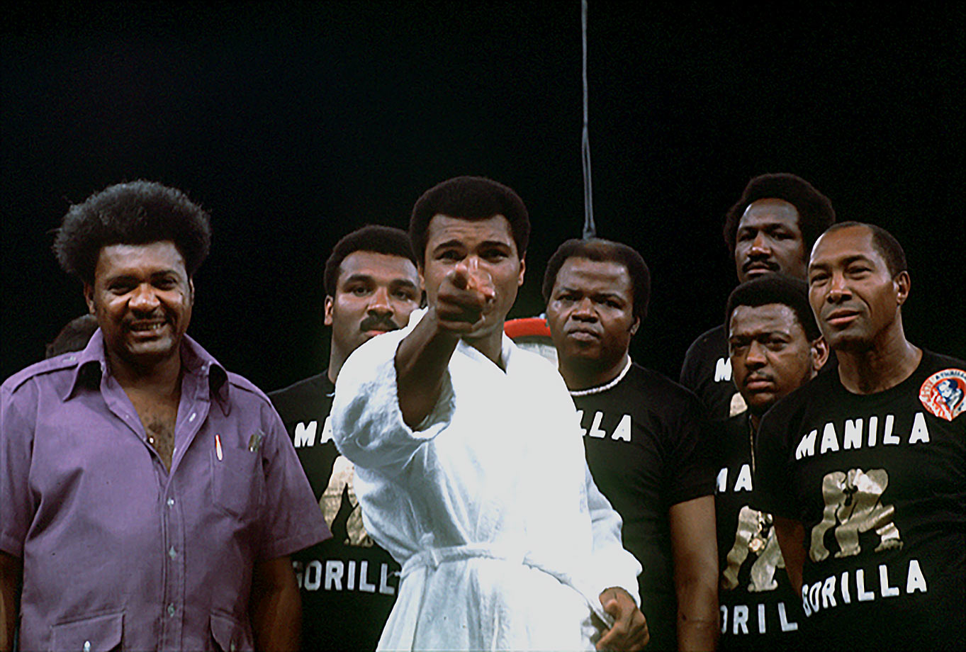 Ali points at the camera with Don King and his training staff behind him before the weigh-in for the Thrilla in Manila in October 1975. Philippine president Ferdinand Marcos offered to sponsor the bout and hold it in Metro Manila to divert attention from the turmoil in the country that had forced the imposition of martial law in 1972.
