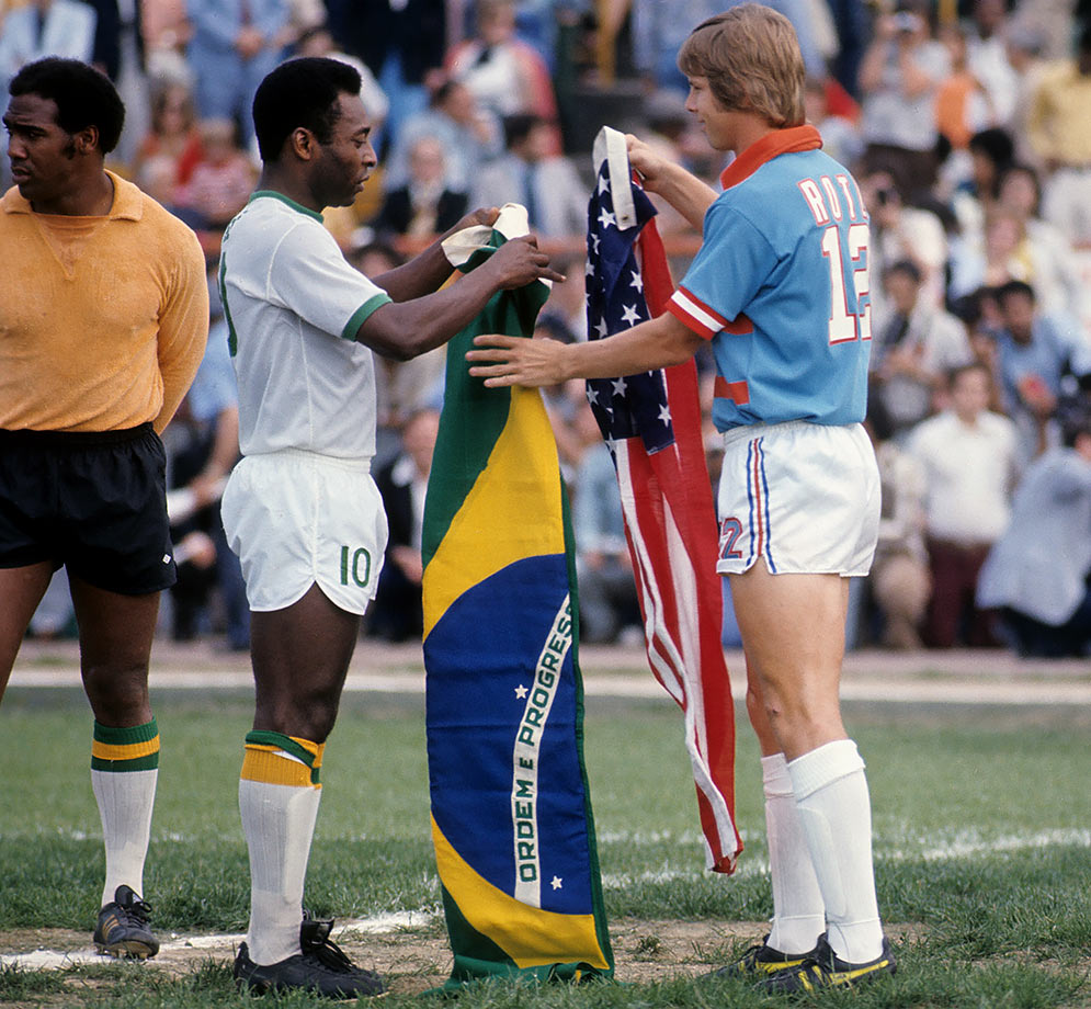 Pelé of the New York Cosmos looks to exchange his Brazilian flag with Kyle Rote Jr. of the Dallas Tornados for his American flag.