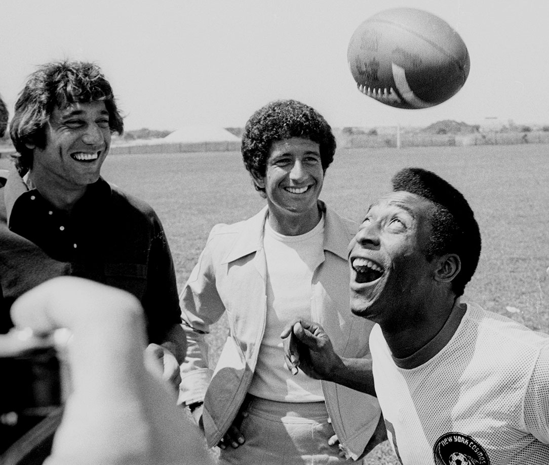 "During a ""Fabrege Promotional Event"" on Aug. 5, 1975, Pelé juggles an American football. His headers were quite amusing, drawing laughs out of spectators Joe Namath and designer Richard Barry."