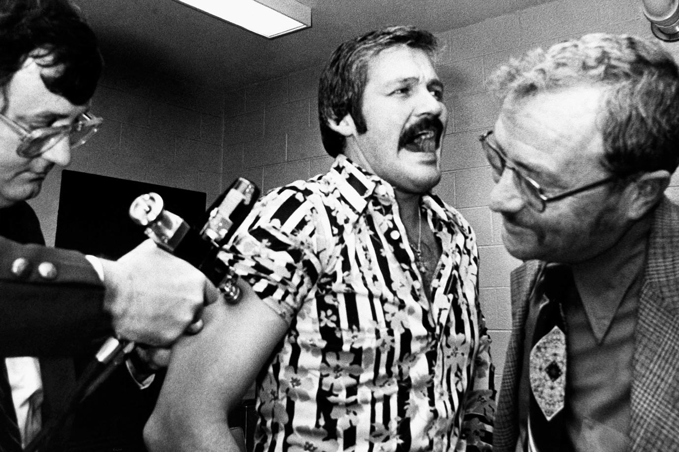 One shot managed to get by Bernie Parent, as he reacts to getting a swine flu immunization shot while Flyers coach Fred Shero watches smiling on Oct. 25, 1976 in Philadelphia.