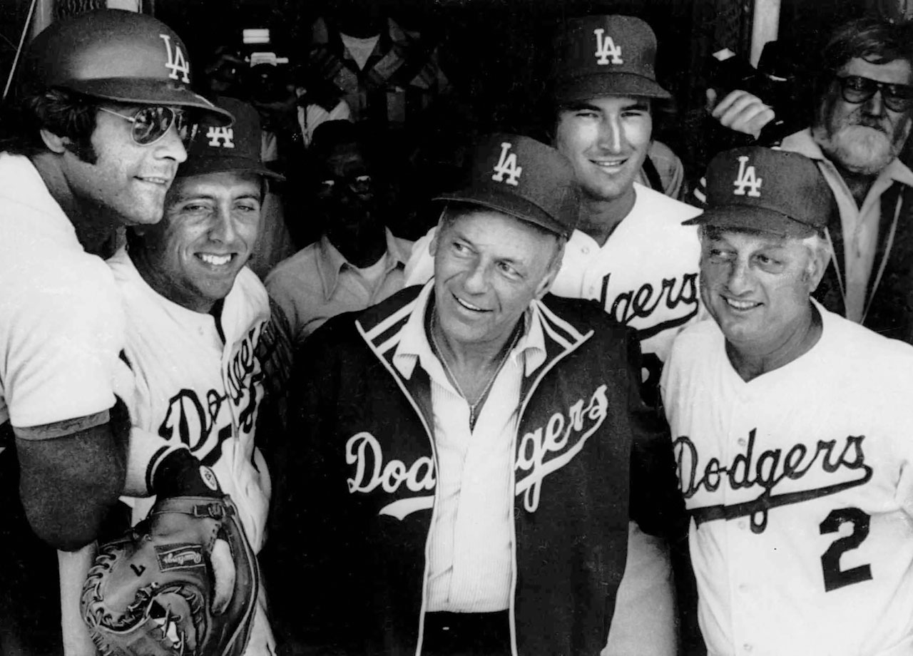 Frank Sinatra poses in the Los Angeles Dodgers dugout with (left to right) players Steve Yeager, Rick Monday, Rick Rhoden and  manager Tommy LaSorda prior to singing the National Anthem for the Dodgers home opener against the San Francisco Giants at Dodger Stadium on April 7, 1977.