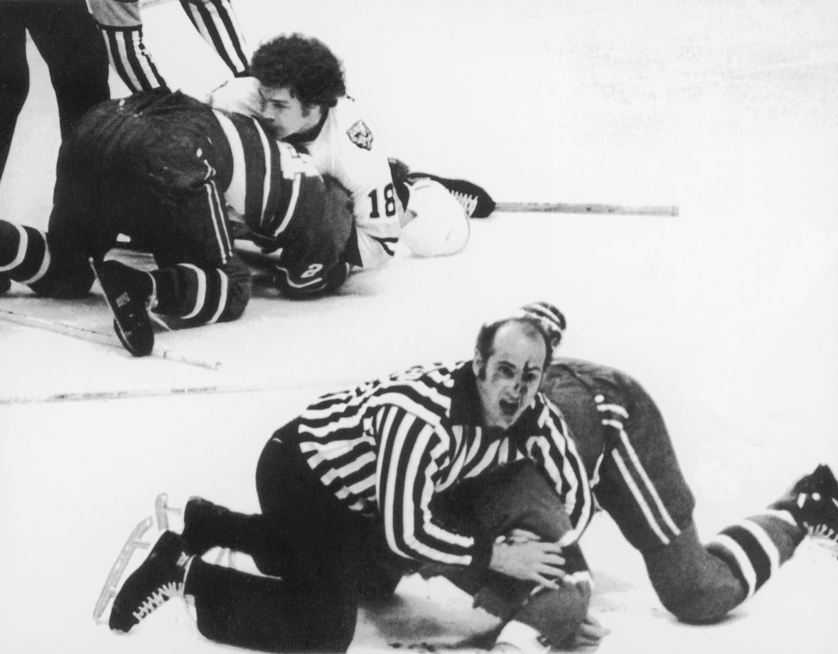 With blood on his face, linesman John D'Amico calls for help as he wrestles Pierre Bouchard of the Montreal Canadiens to the ice after a fight. In the background, a second official breaks up a fight between John Wensink (18) of the Boston Bruins and the Canadiens' Gilles Lupien. Though Boston won the game, Montreal went on to win the series and the Cup four games to two.