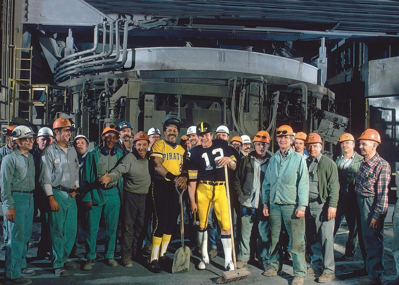 Terry Bradshaw and Willie Stargell were the toast of the town in 1979 after leading their respective teams to a championship. Here they pose with workers at Jones & Laughlin steel mill in Pittsburgh.