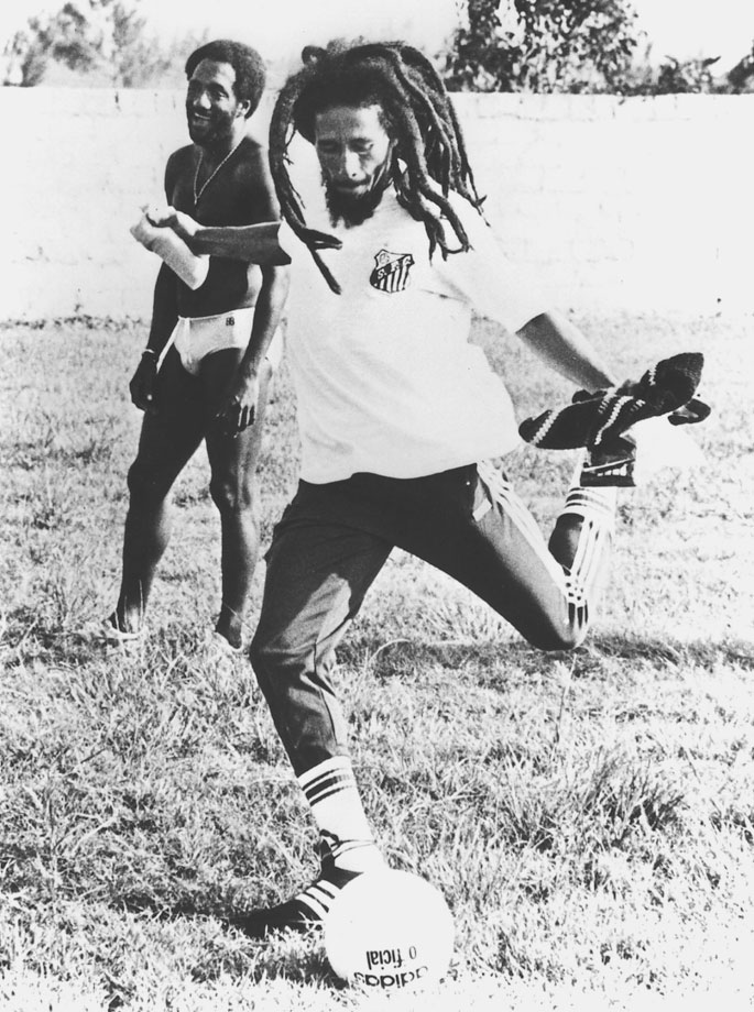 Bob Marley looks to kick a soccer ball as Brazil's Paulo Cezar Caju looks on in May 1980.