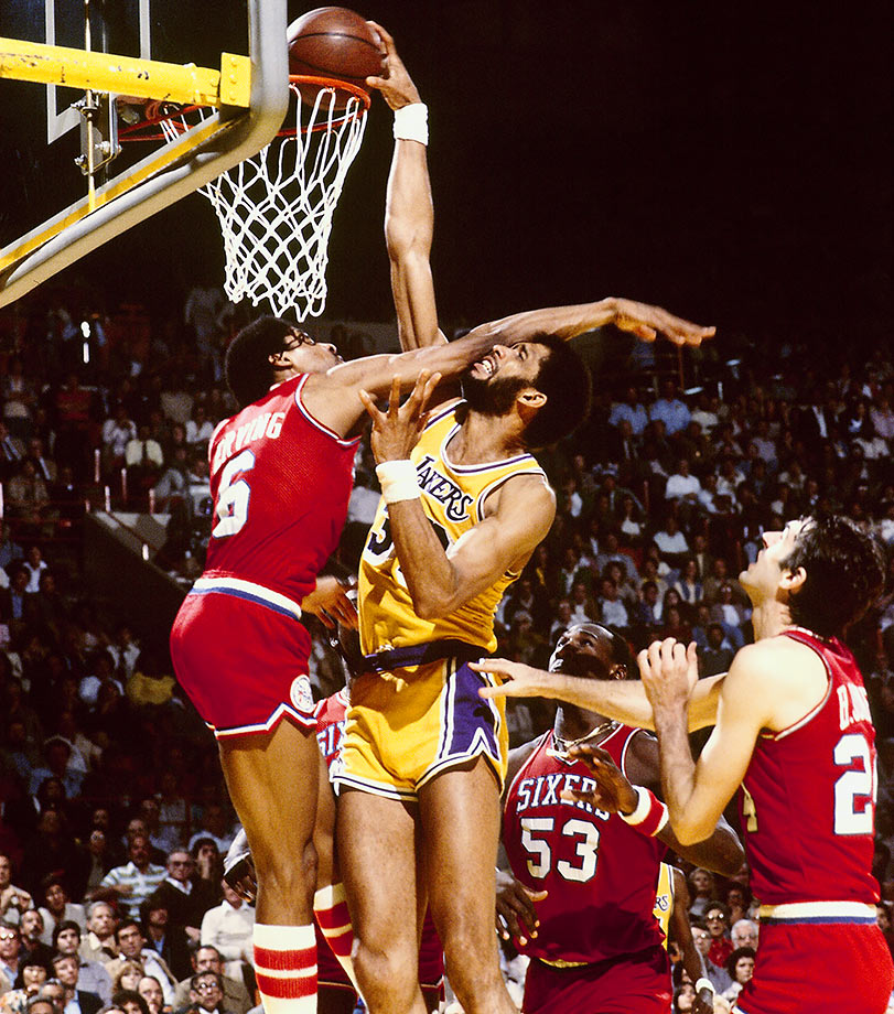 Usually the player doing the dunking, Dr. J gets posterized by Kareem Abdul-Jabbar.