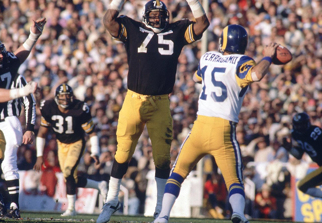 Pittsburgh Steelers defensive tackle Joe Greene leaps as Los Angeles Rams quarterback Vince Ferragamo attempts to get a pass off. Mean Joe starred in his famous Coca-Cola ad during the commercials of the game, a 31-19 Steelers victory.