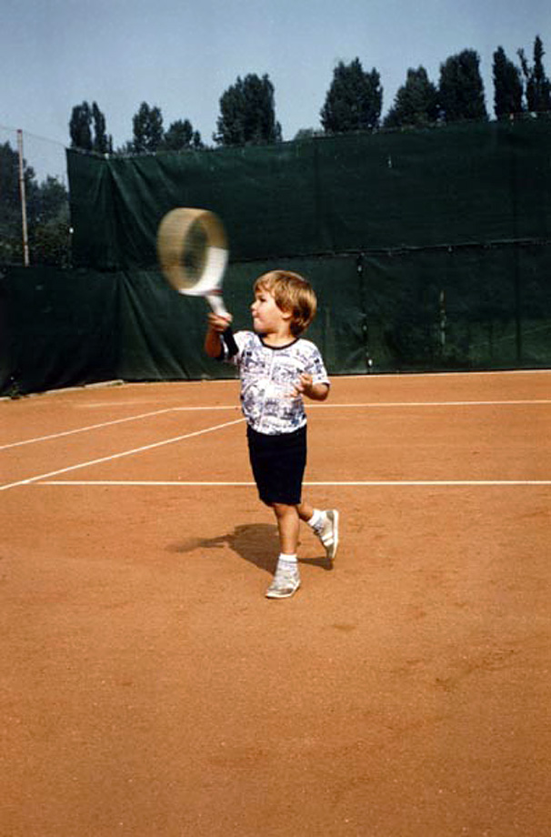 A very young Roger Federer takes to the court.