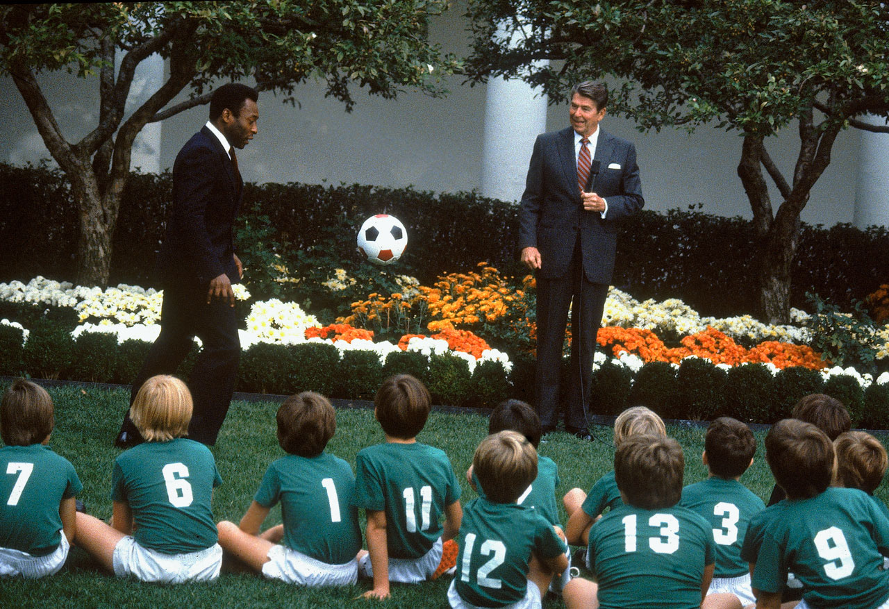 Pelé kicks a ball in front of a local boys soccer team as President Ronald Reagan looks on in the Rose Garden at the White House on Oct. 14, 1982.