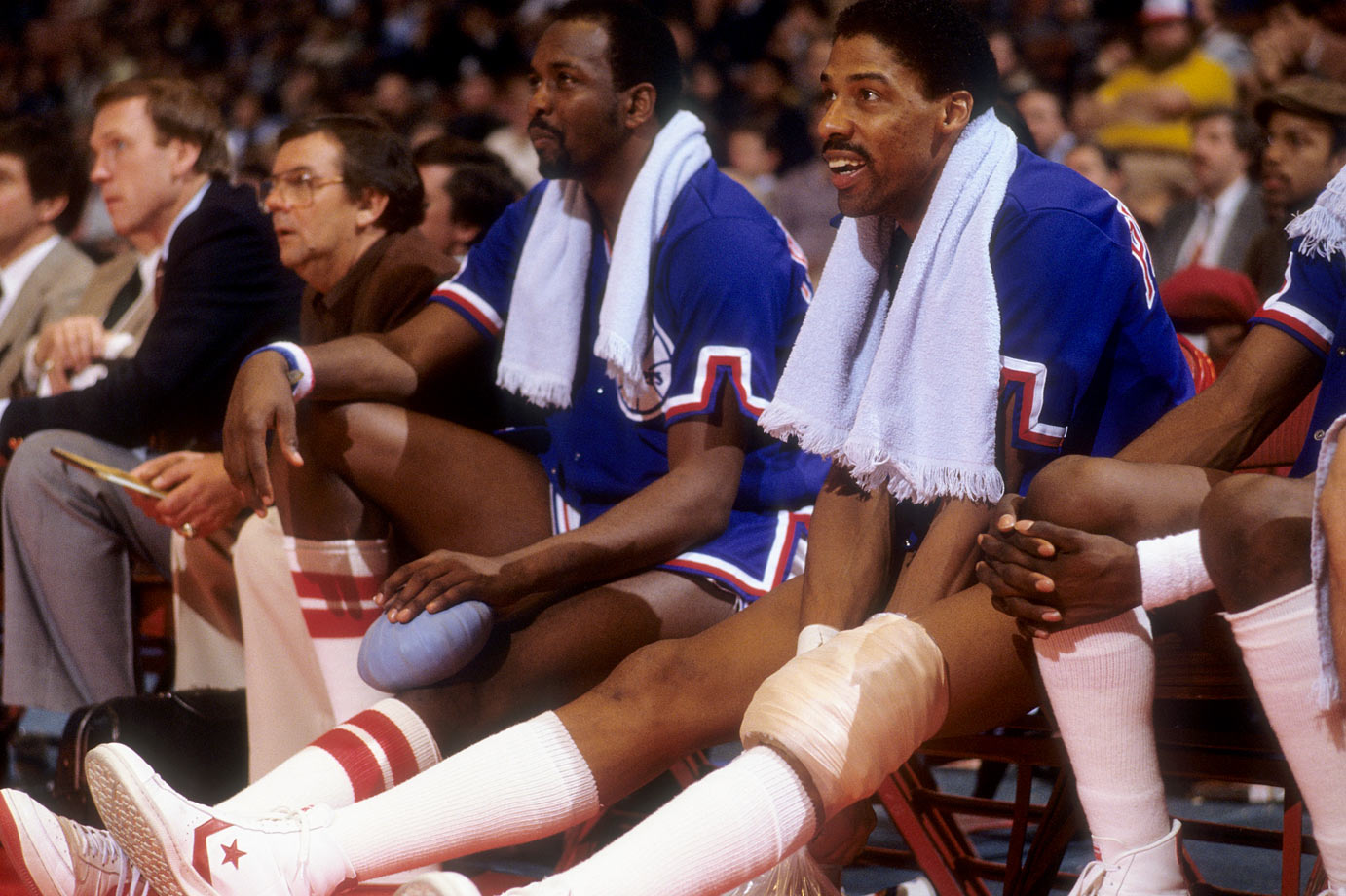 Dr. J and Moses Malone watch the action from the bench.