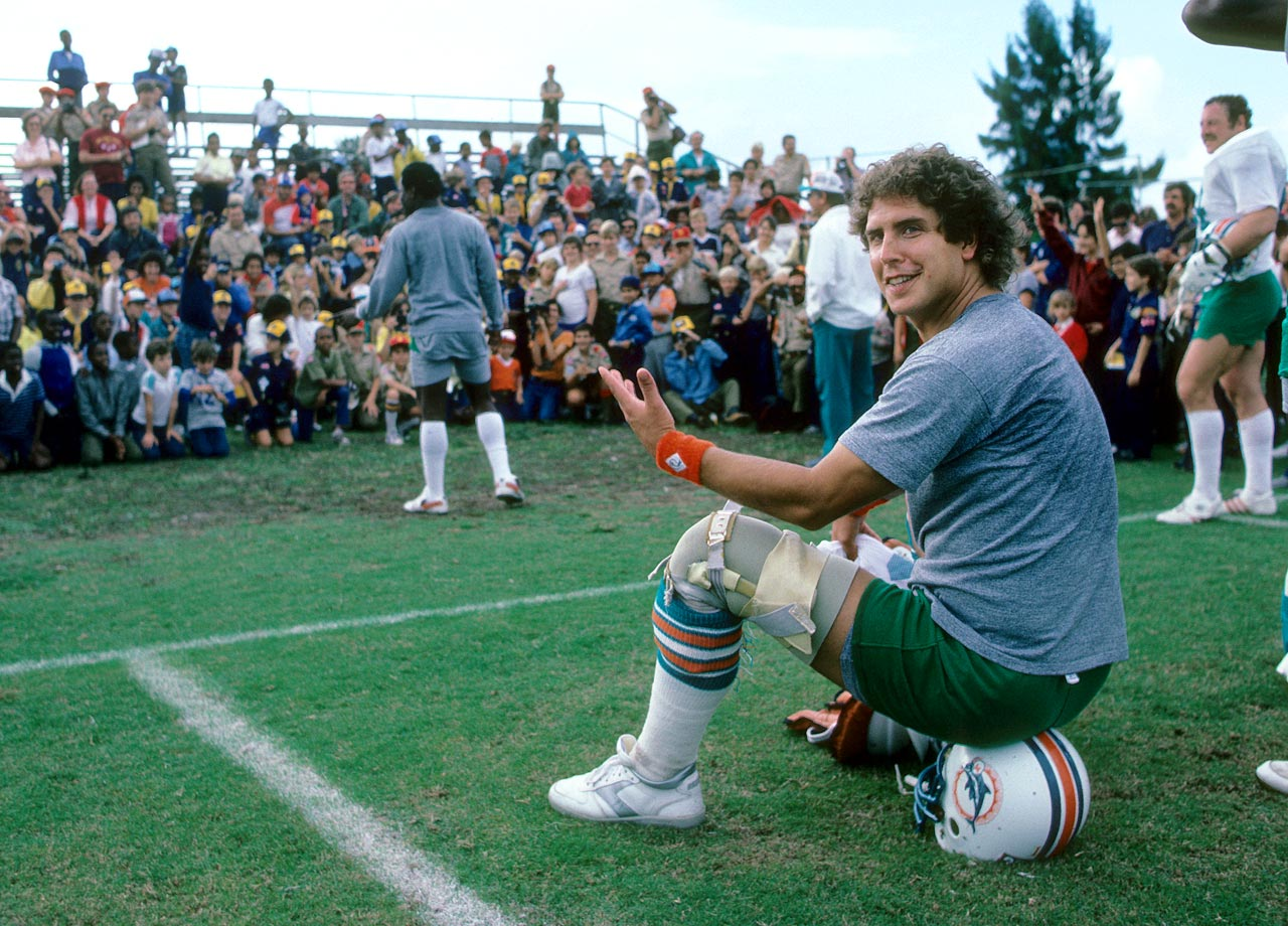 Dan Marino sits on his helmet during practice at St. Thomas University in Miami on Nov. 26, 1984.