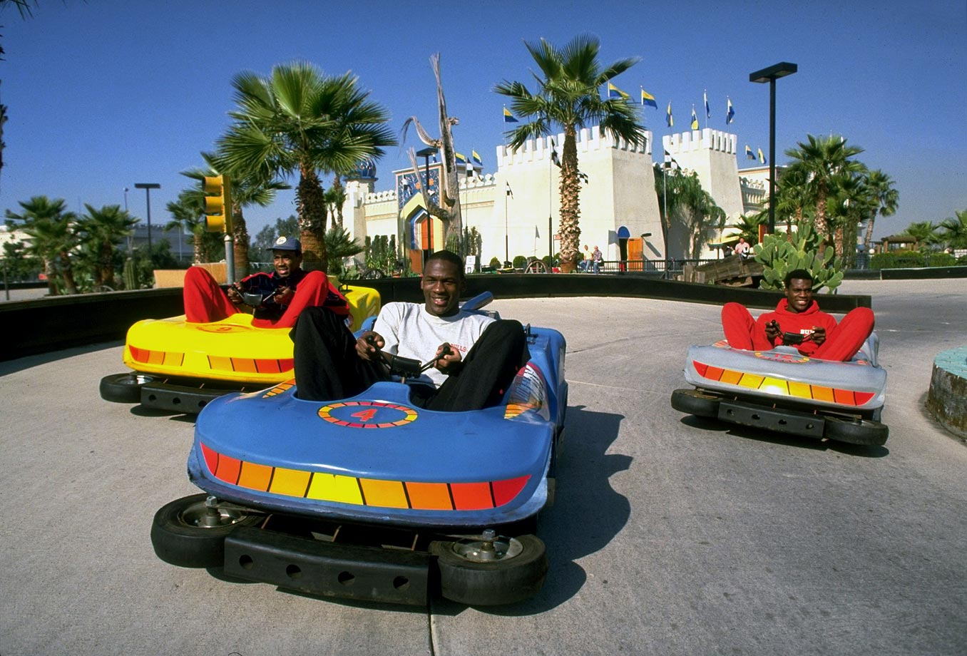 Michael Jordan drives a bumper car against Bulls teammates Rod Higgins and Orlando Woolridge at an amusement park in Phoenix in November 1984.