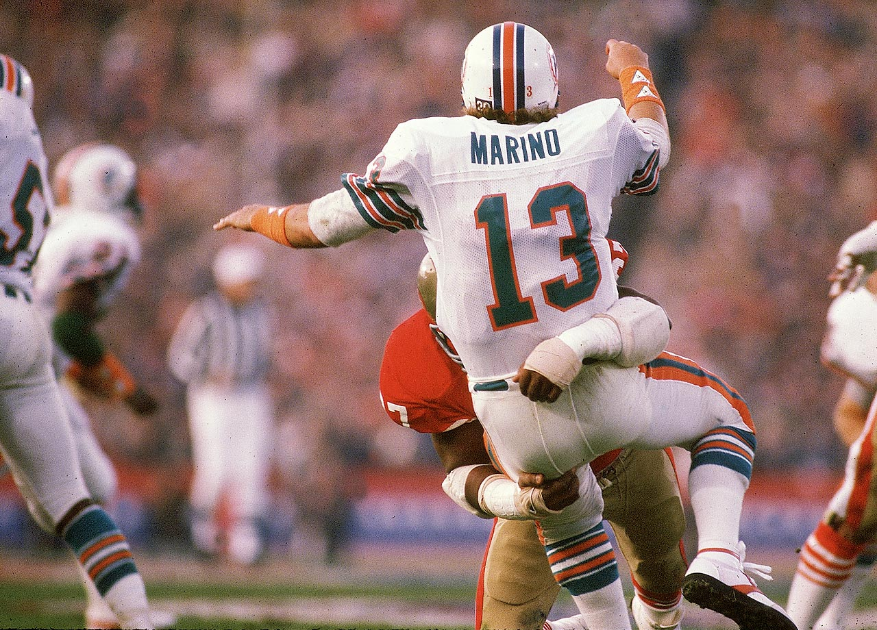 Dan Marino absorbs a big hit from San Francisco 49ers defensive tackle Gary Johnson. Marino completed 29 of 50 passes for 318 yards and a touchdown but his Miami Dolphins fell 38-16.