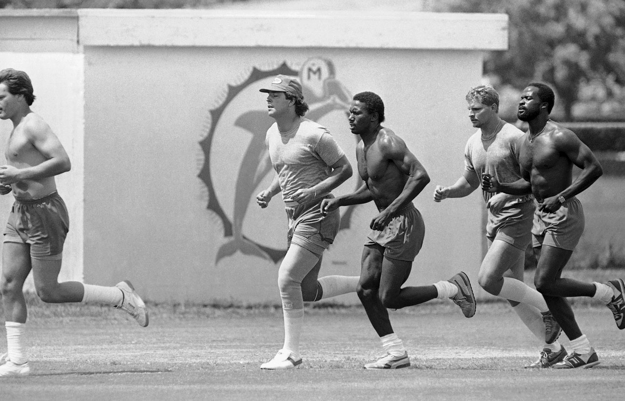 Miami quarterback Dan Marino and teammates struggle through a 12-minute run at Dolphins' training camp in Miami.