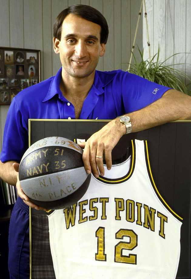 Mike Krzyzewski poses with his retired #12 West Point jersey and a game ball from Army's 51-35 regular season victory over Navy during the 1968-69 season. Krzyzewski was the head coach at Army from 1975 to 1980.