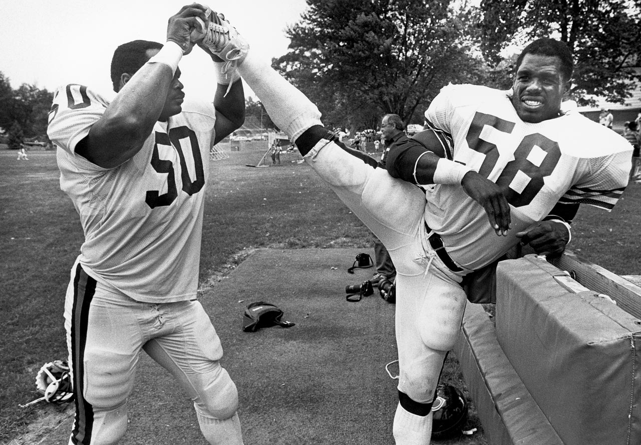Mike Singletary helps teammate Wilber Marshall stretch during Bears training camp at the University of Wisconsin-Platteville.