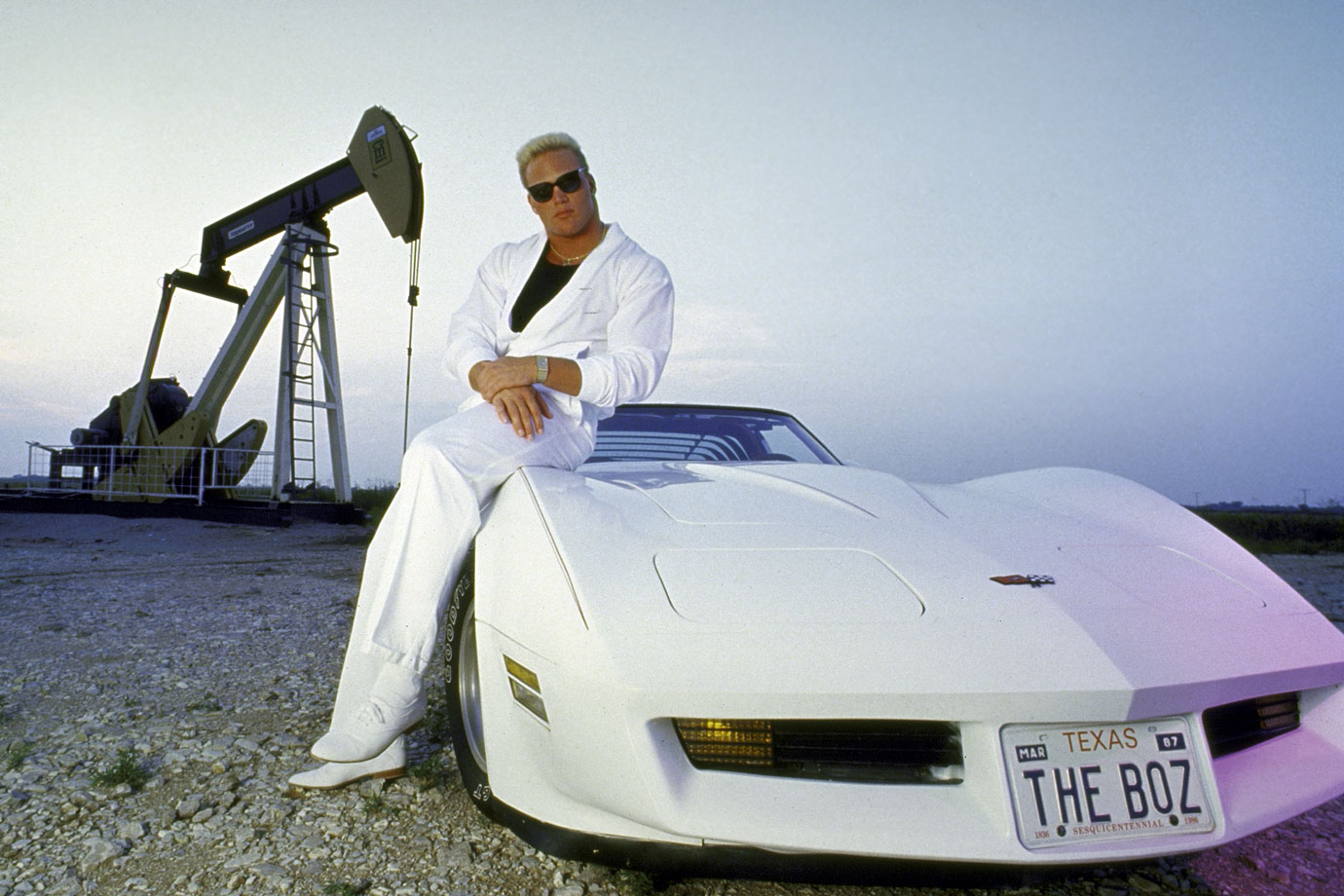 Brian Bosworth leans against his white Corvette.