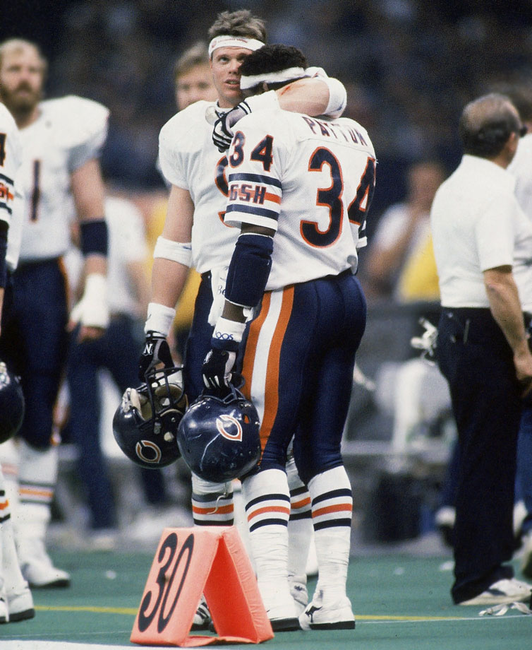Bears quarterback Jim McMahon puts his arm around teammate Walter Payton on the sidelines during Super Bowl XX in New Orleans on Jan. 26, 1986.  Chicago dominated New England 46-10.
