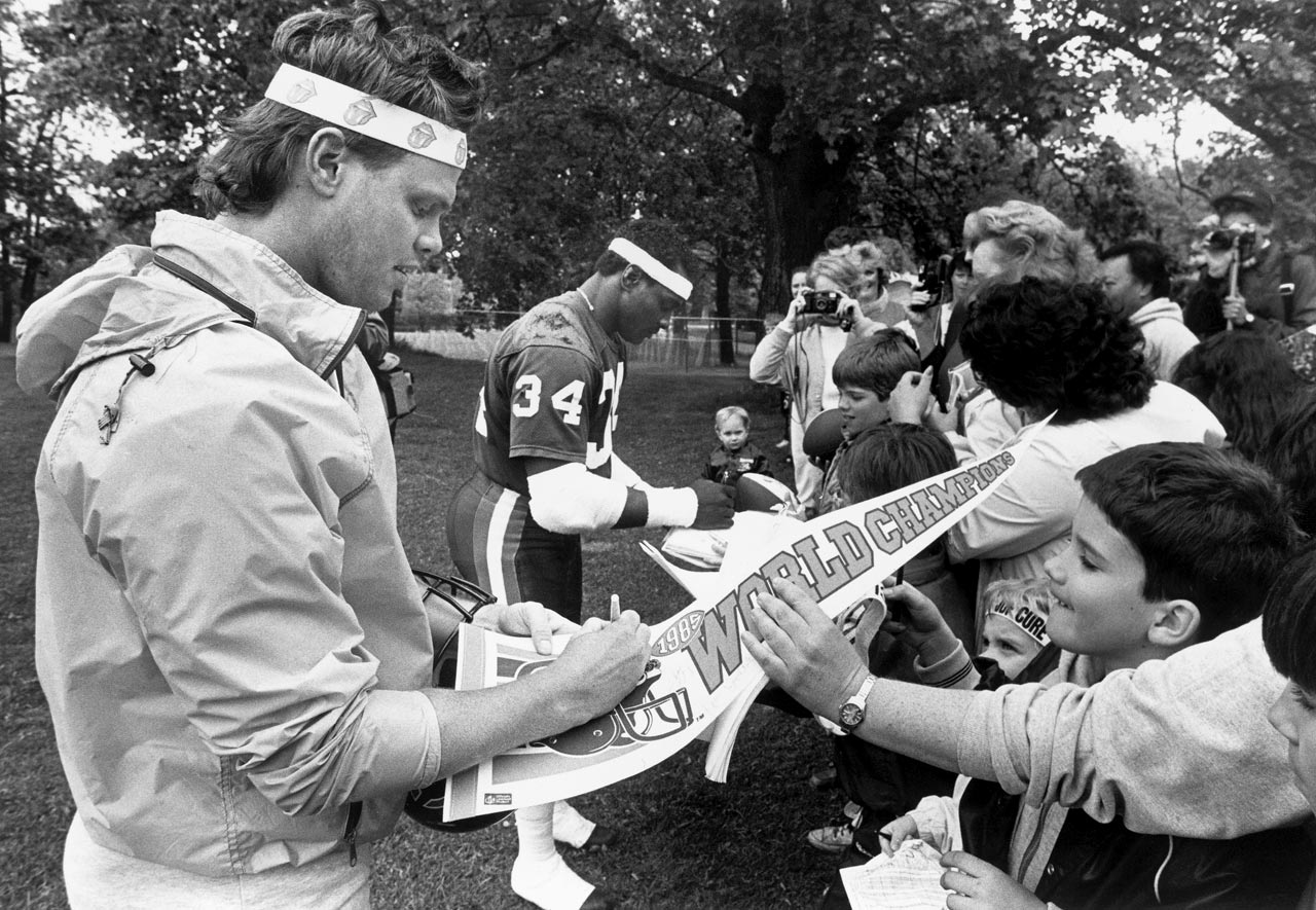 Jim McMahon and Walter Payton sign autographs for fans during training camp at the University of Wisconsin-Platteville.