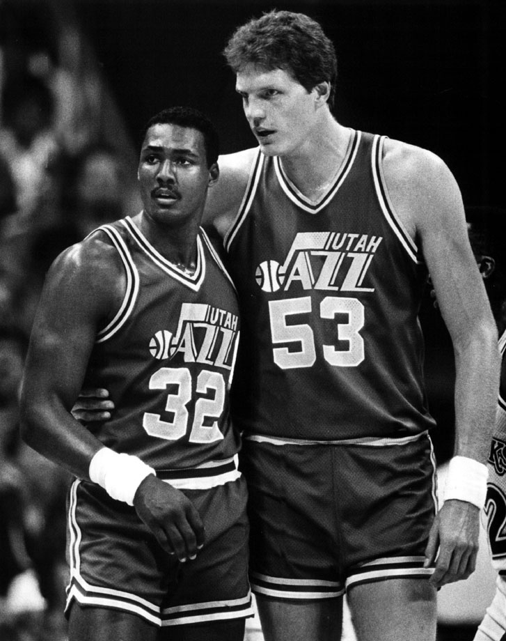 "6' 9"" Karl Malone appears diminutive standing next to 7' 4"" teammate Mark Eaton, one of the tallest players in NBA history."