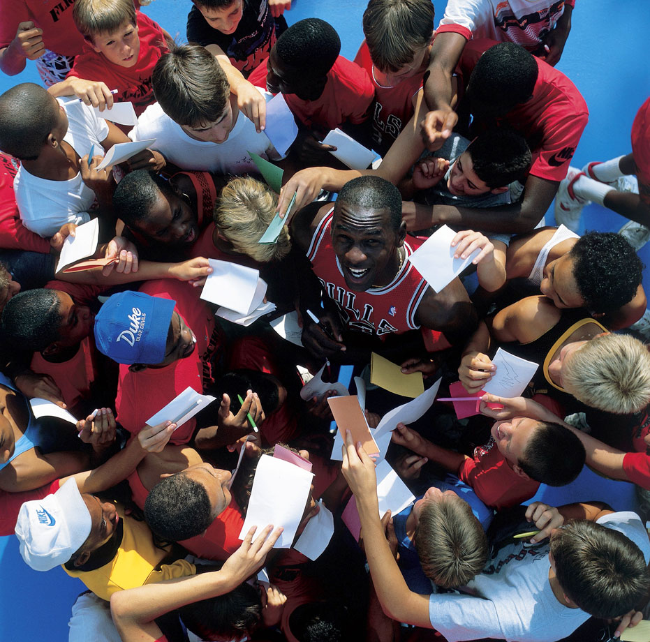 Young autograph seekers surround Michael Jordan at a basketball camp in March 1987. With his on-court success and successful off-court marketing, Jordan quickly became one of the NBA's biggest stars.