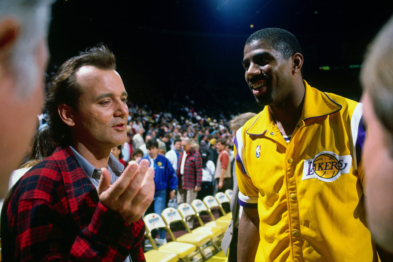 Bill Murray talks with Magic Johnson before a Los Angeles Lakers game in 1988 at the Great Western Forum in Inglewood, Calif.