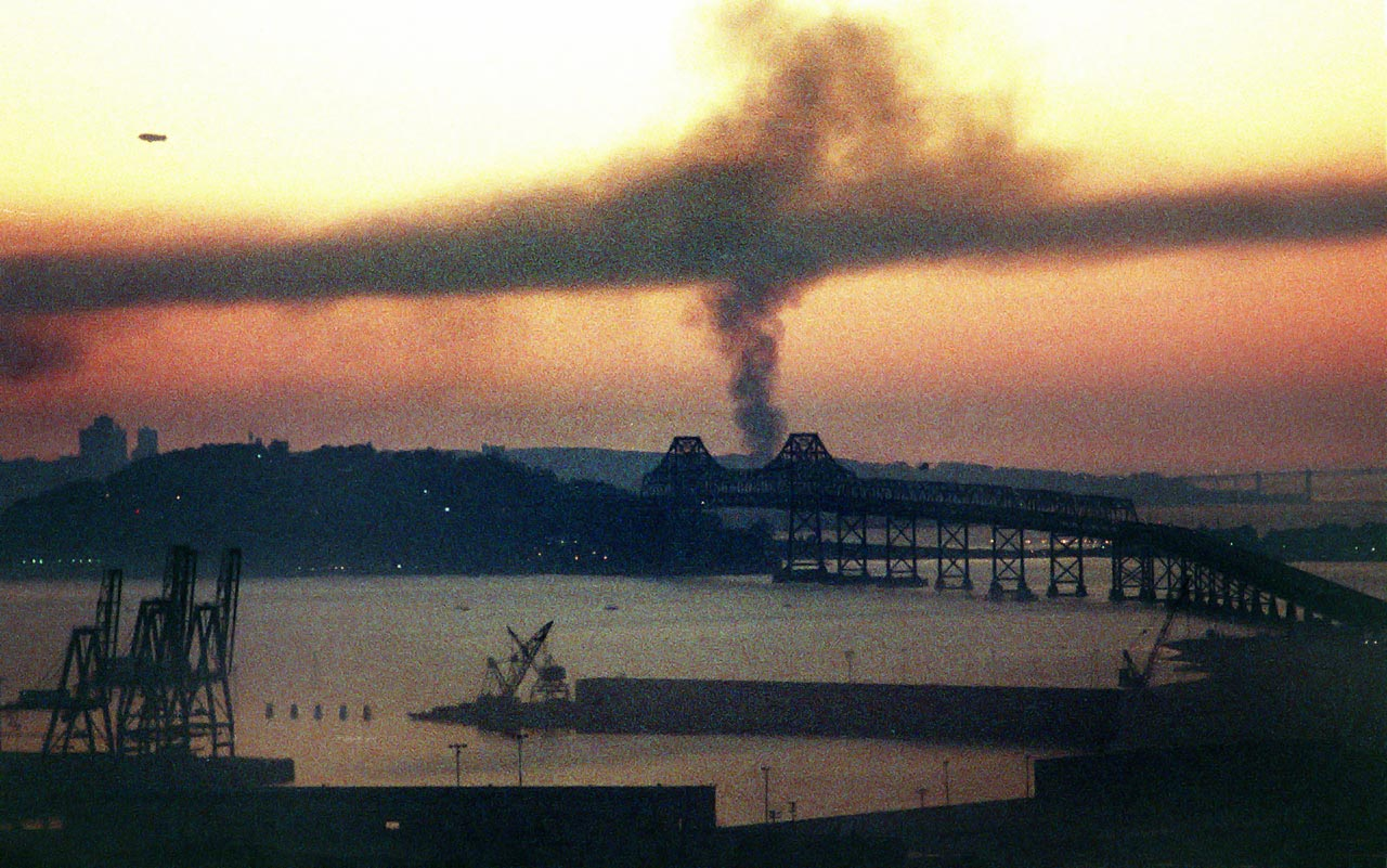 Smoke rises behind the Bay Bridge from a fire in San Francisco's Marina District caused by the earthquake.  The blimp (upper left) was in town for the World Series game at Candlestick Park.  One section of the upper deck Bay Bridge collapsed due to the quake.