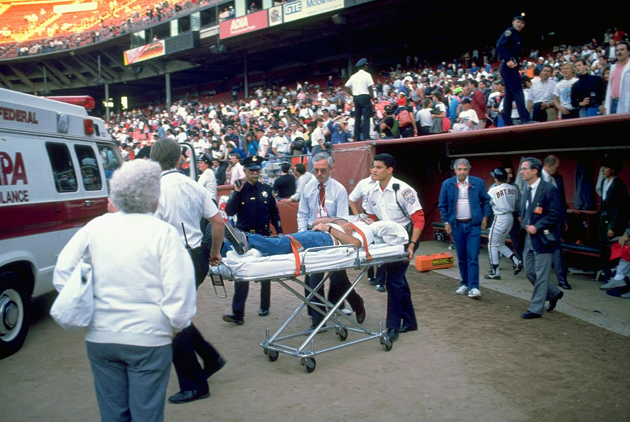 An angina victim is wheeled off the field on a stretcher at Candlestick Park after the earthquake.
