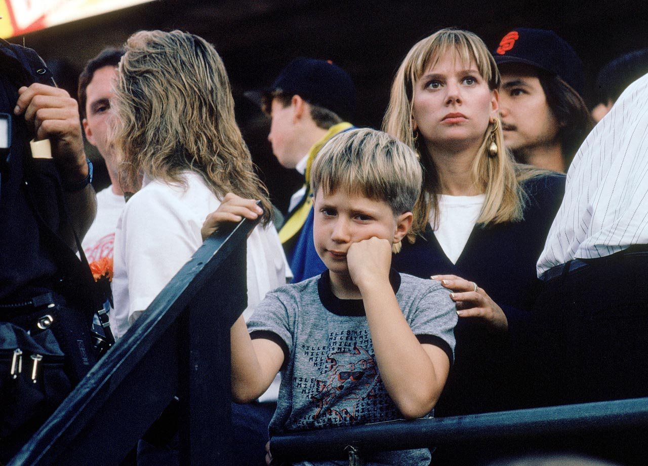 A young dejected baseball fan looks on after the postponement of Game 3 of the World Series.