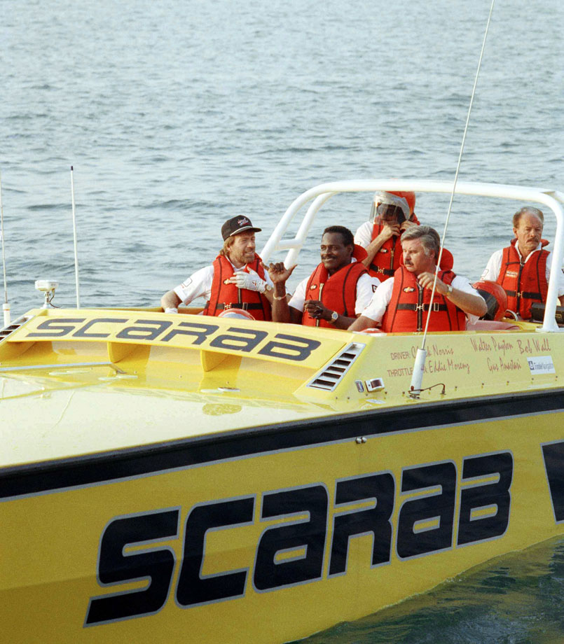 Chuck Norris, Walter Payton and throttle man Eddie Morenz prepare to depart from Chicago's Navy Pier on a 605-mile speed boat trip across Lakes Michigan and Huron in Chicago on July 27, 1989. The team hoped but failed to break a 1987 speed record for the trip to Detroit while raising funds for the United Way.