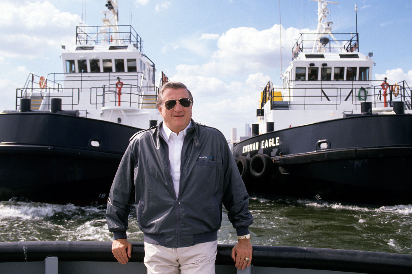 George Steinbrenner poses in front of tugboats along a dock for the American Ship Building Company on May 3, 1990 in Tampa, Fla.
