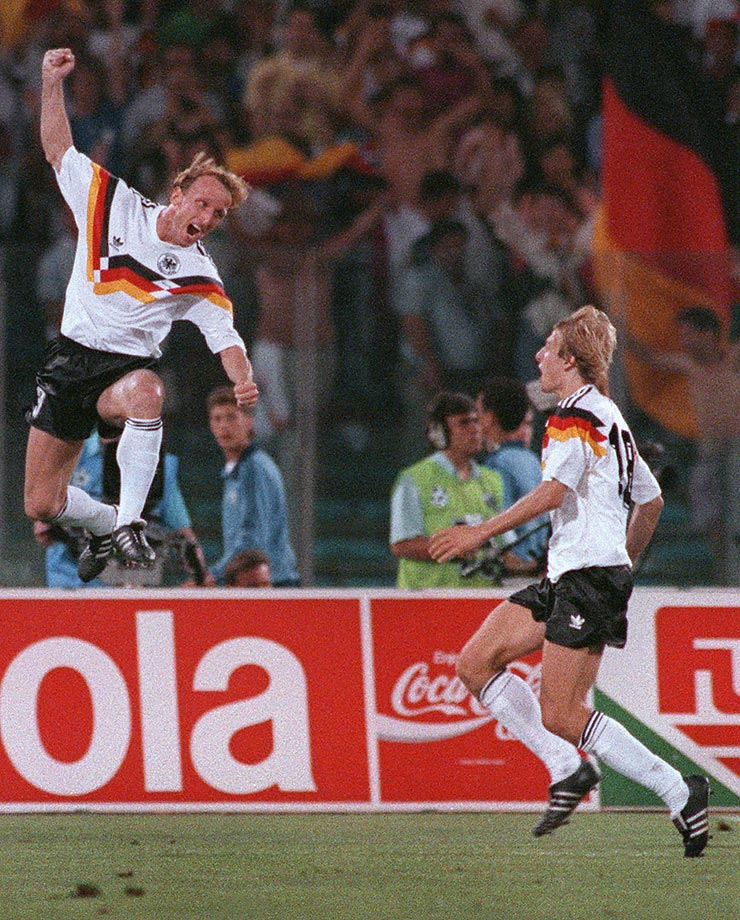 Andreas Brehme celebrates in front of teammate Jürgen Klinsmann after scoring the winning goal on a penalty kick during the 1990 World Cup final.